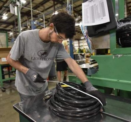 Zach Harness, 17, a student at Villa Rica High School, works at packing a product at a Carrollton plant. AJC photo.